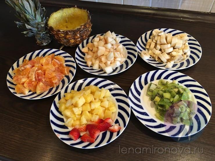 нарезанные апельсин, ананас, банан, киви, груша на тарелках