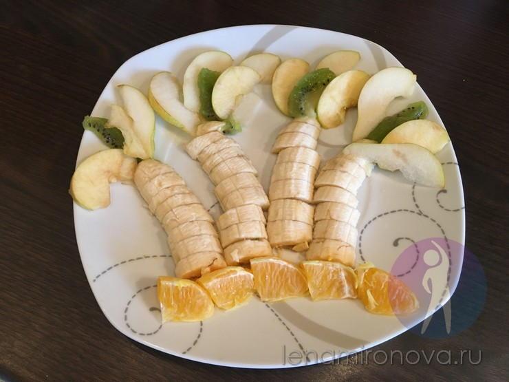 выкладка бананов, яблок и апельсина на тарелке